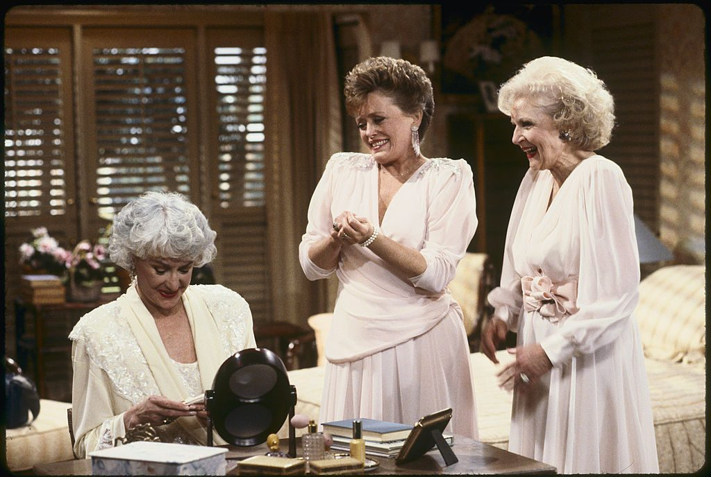Bea Arthur, Rue McClanahan and Betty White wearing white dresses and smiling