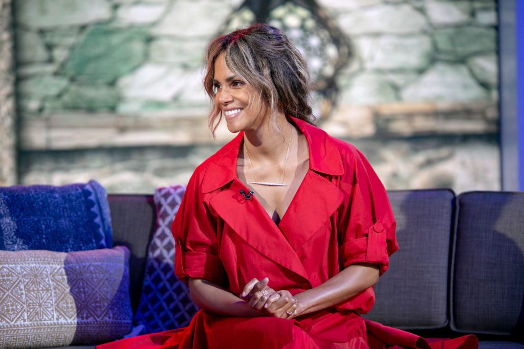 Halle Berry in red smiling, sitting on a couch.