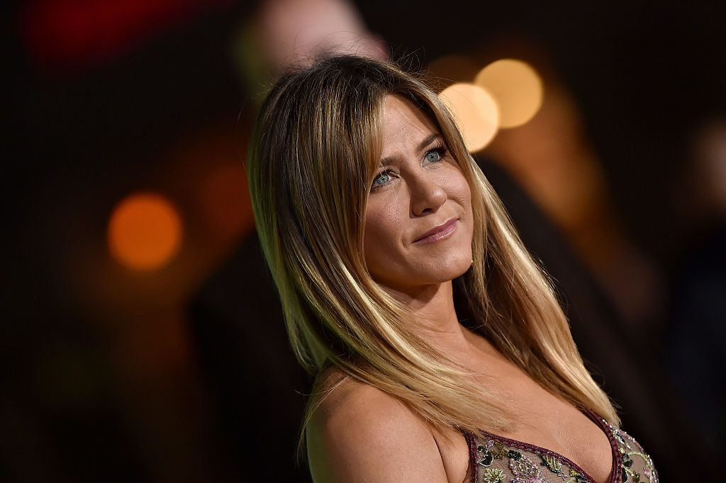 Jennifer Aniston smiling in front of blurred backdrop