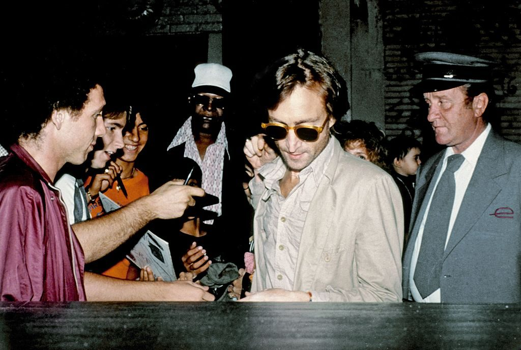John Lennon in a crowd of people getting into a car