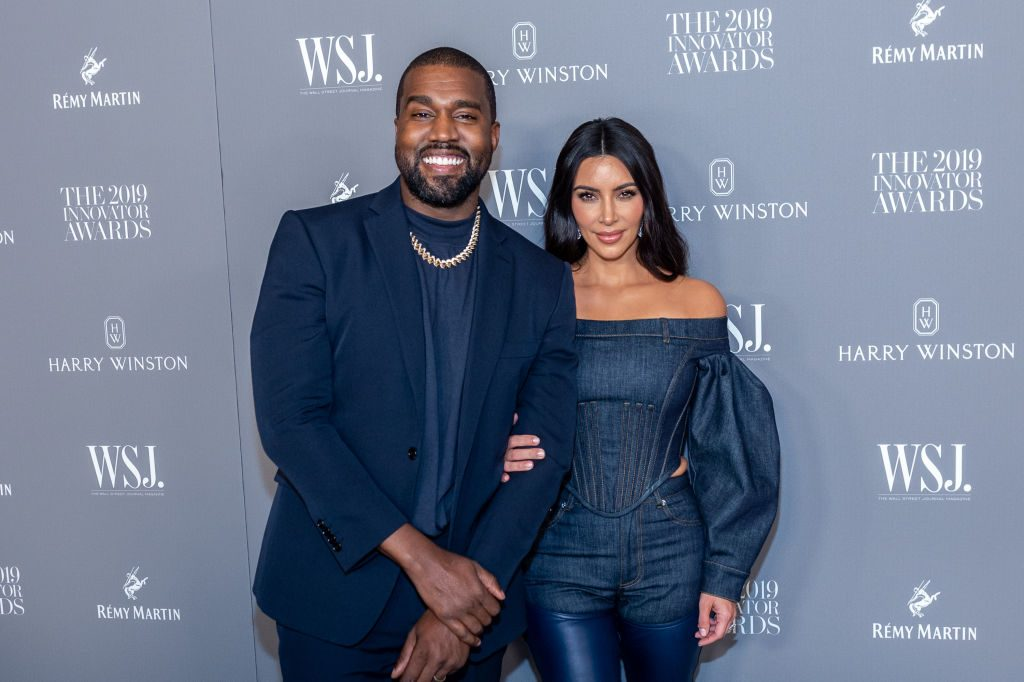 Kanye West and Kim Kardashian West pose together at an event in matching navy blue outfits.