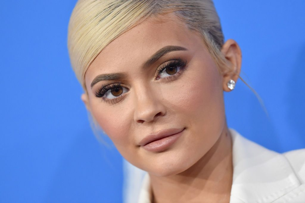 Kylie Jenner in front of blue backdrop.