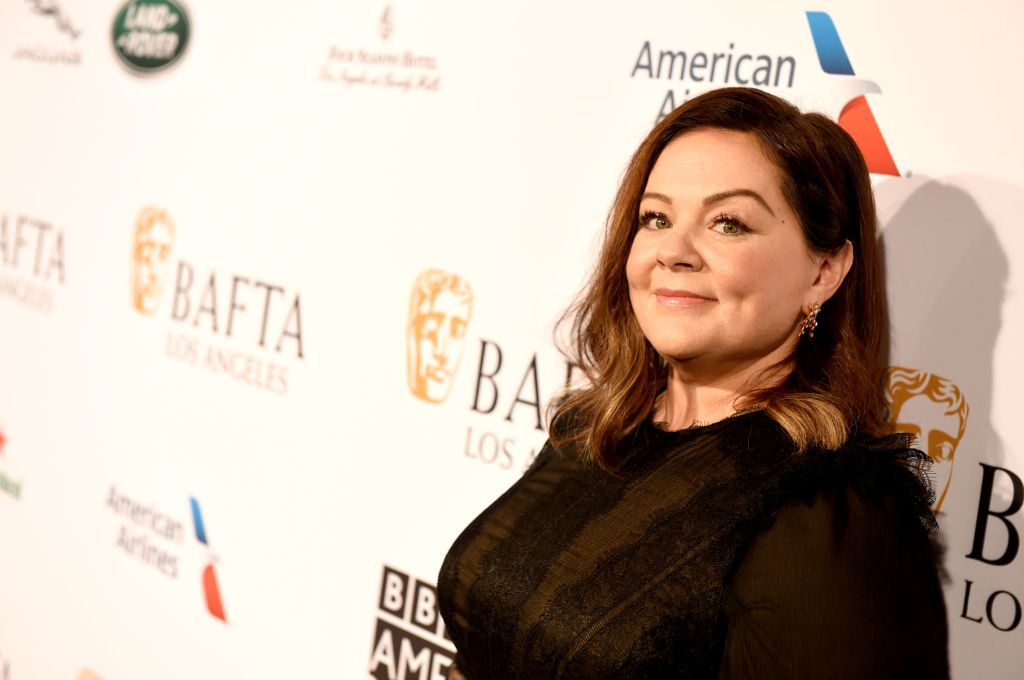 Melissa McCarthy wearing black in front of a repeating background