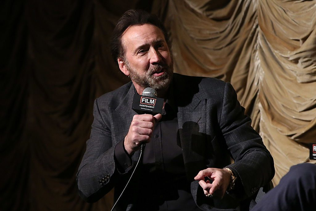 Nicolas Cage holding a microphone in front of a velvet yellow curtain