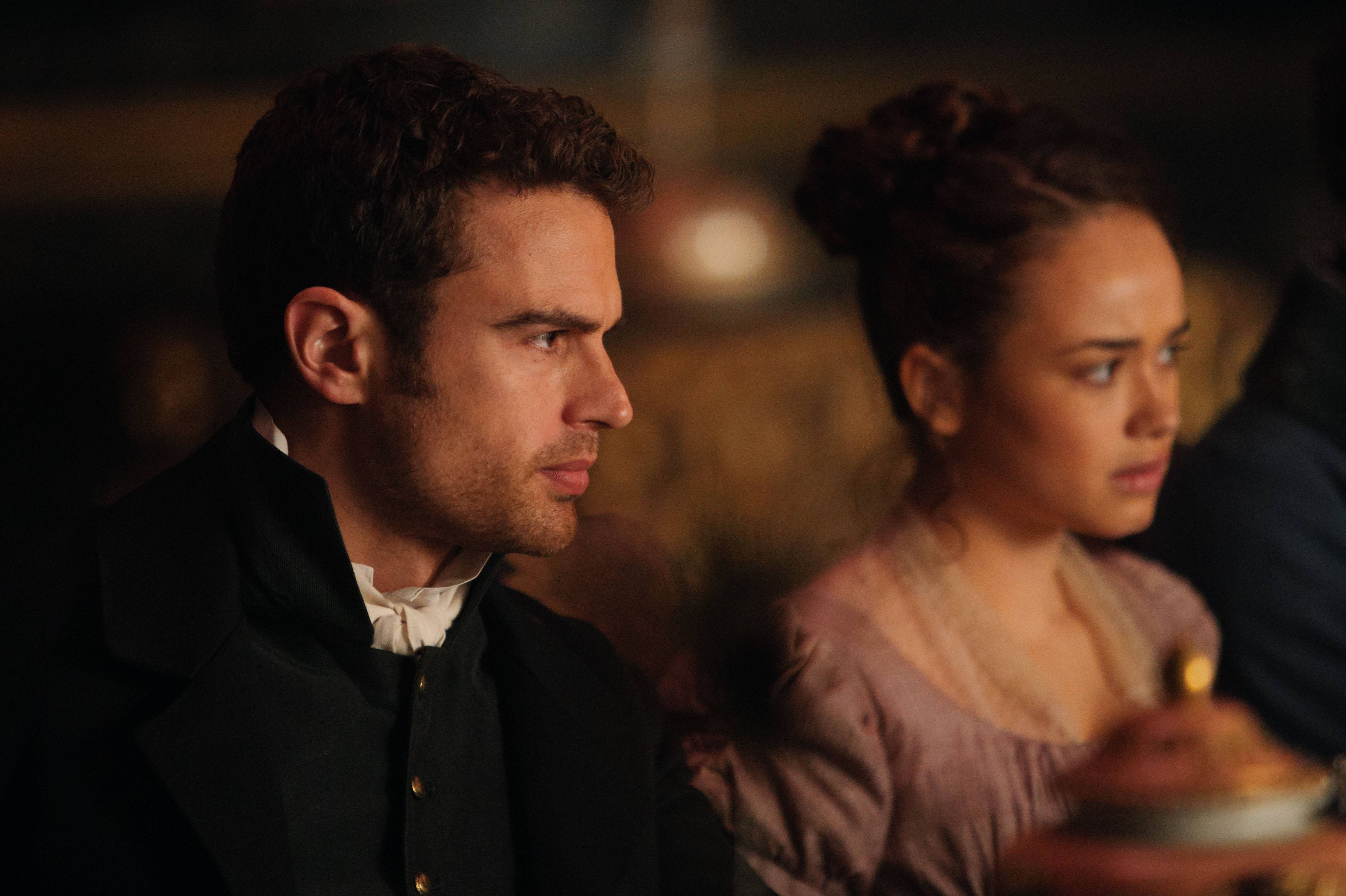 Theo James as Sidney and Rose Williams as Charlotte, in profile and sitting at a table, in 'Sanditon'