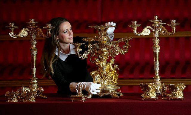 A member of Buckingham Palace's staff poses with items from Royal Collection on March 16, 2015