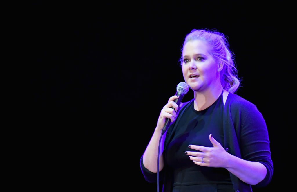 Amy Schumer on stage holding a microphone