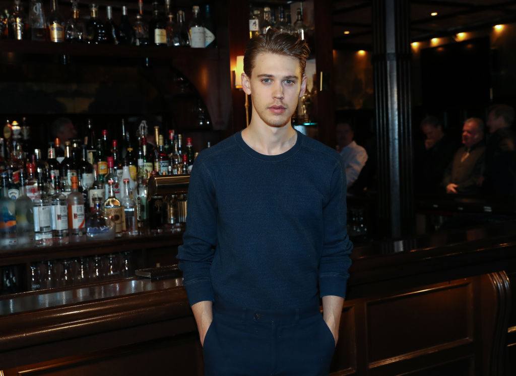 Austin Butler in navy blue standing in front of a bar