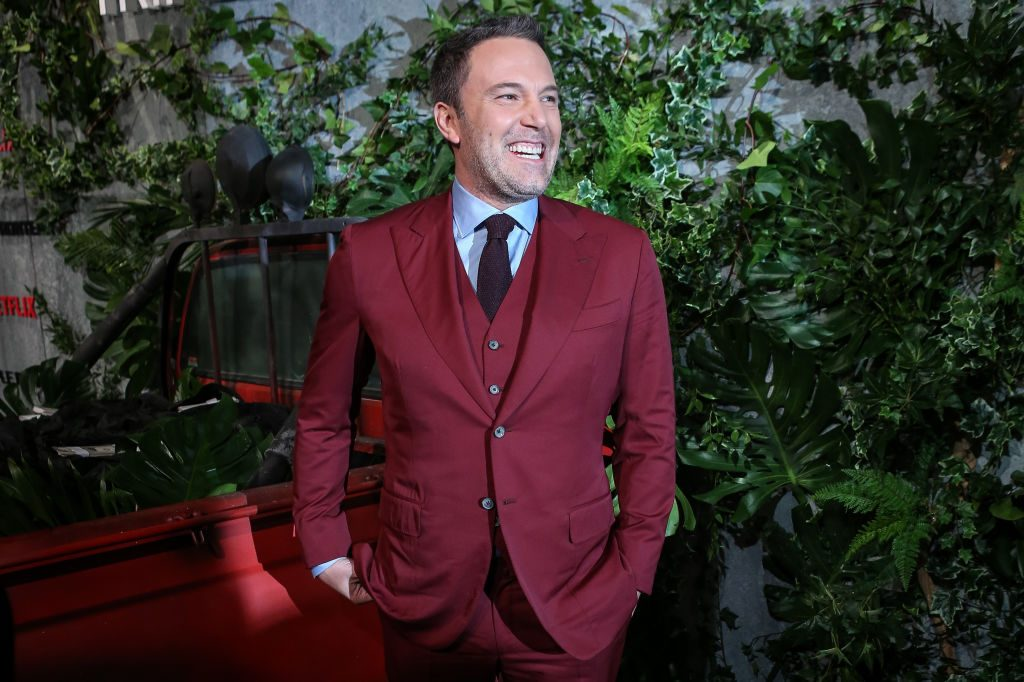 Ben Affleck in a dark red suit laughing in front of greenery