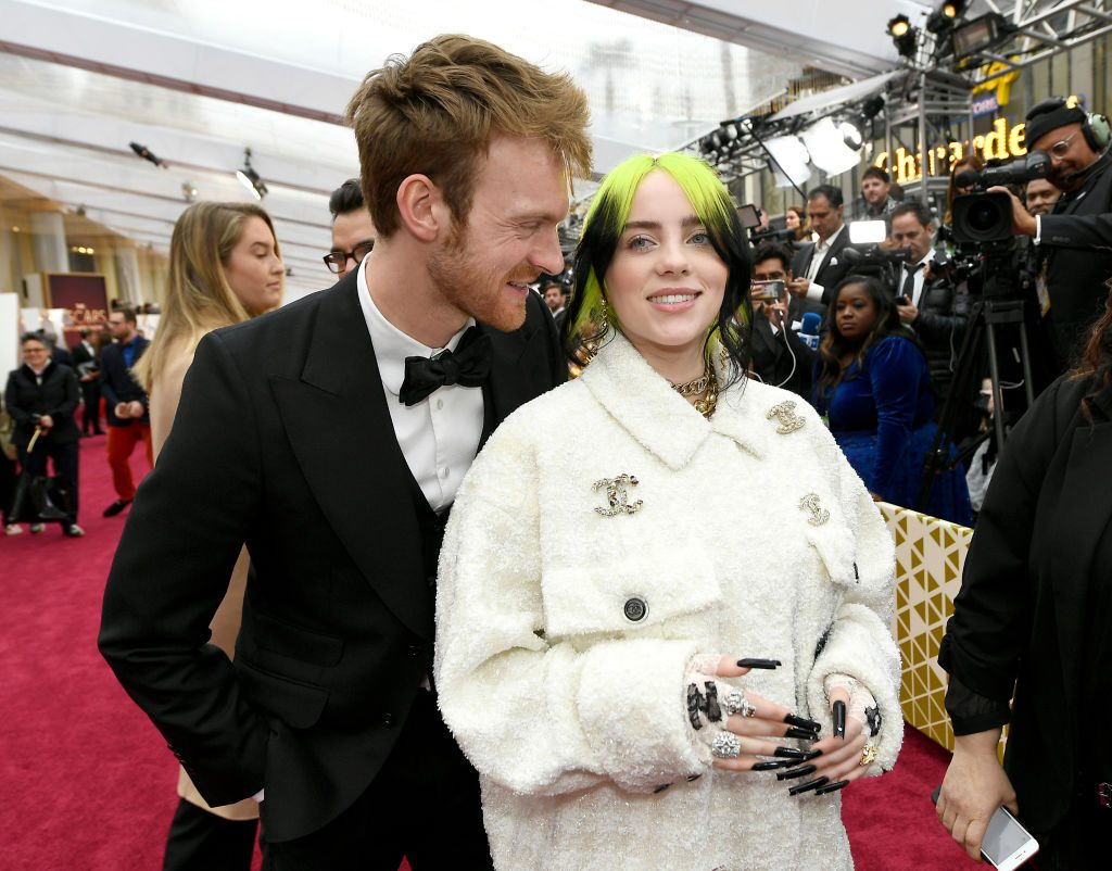 Billie Eilish wearing a white collared Chanel jacket standing in front and to the right of her brother, Finneas O'Connell