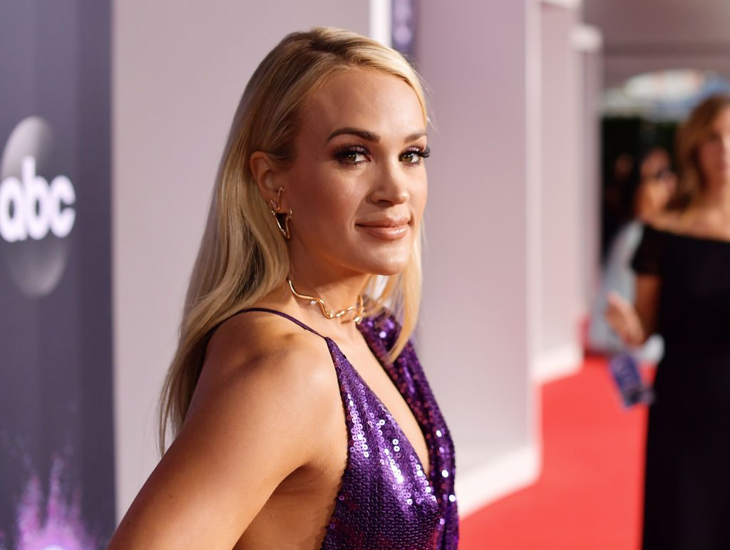 Carrie Underwood in purple, smiling at the camera in front of a repeating background