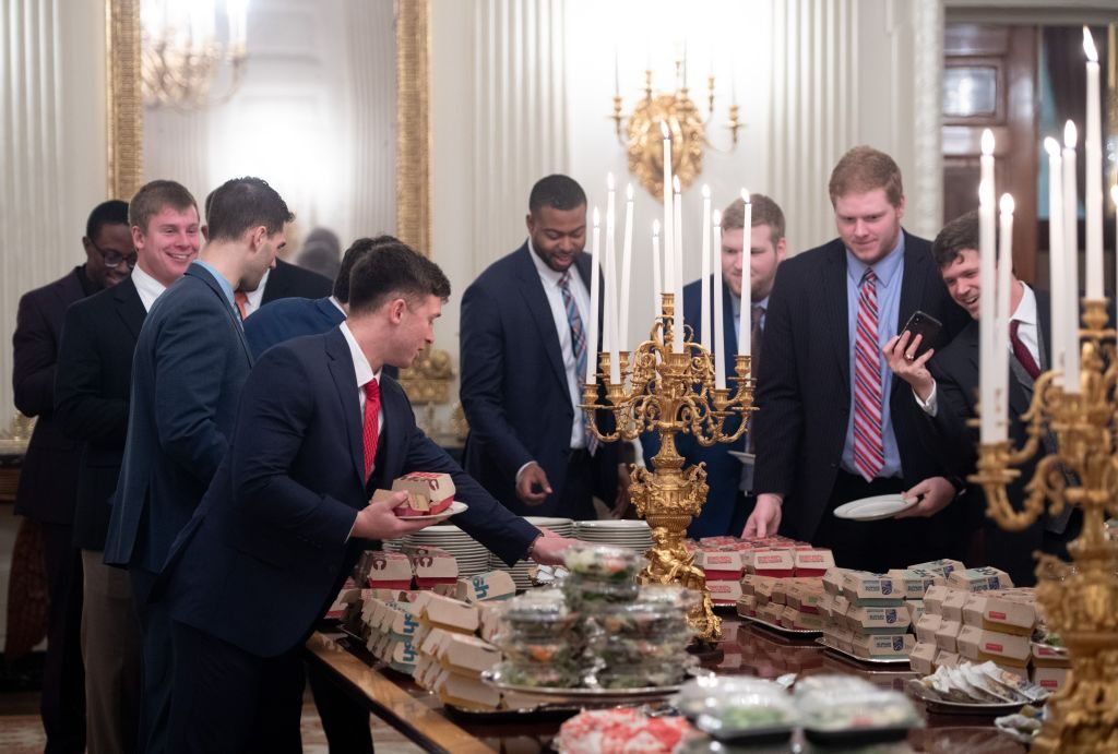 Guests select fast food that the US president purchased for a ceremony honoring the 2018 College Football Playoff National Champion Clemson Tigers in the State Dining Room
