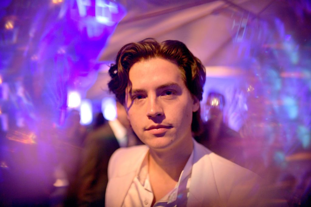 Cole Sprouse in the middle of blurred purple lighting