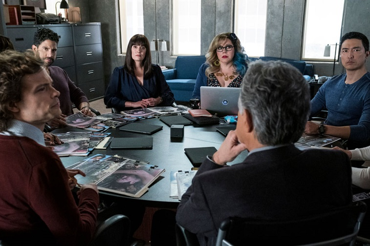 Cast members sit around a table while filming for Criminal Minds season 15.