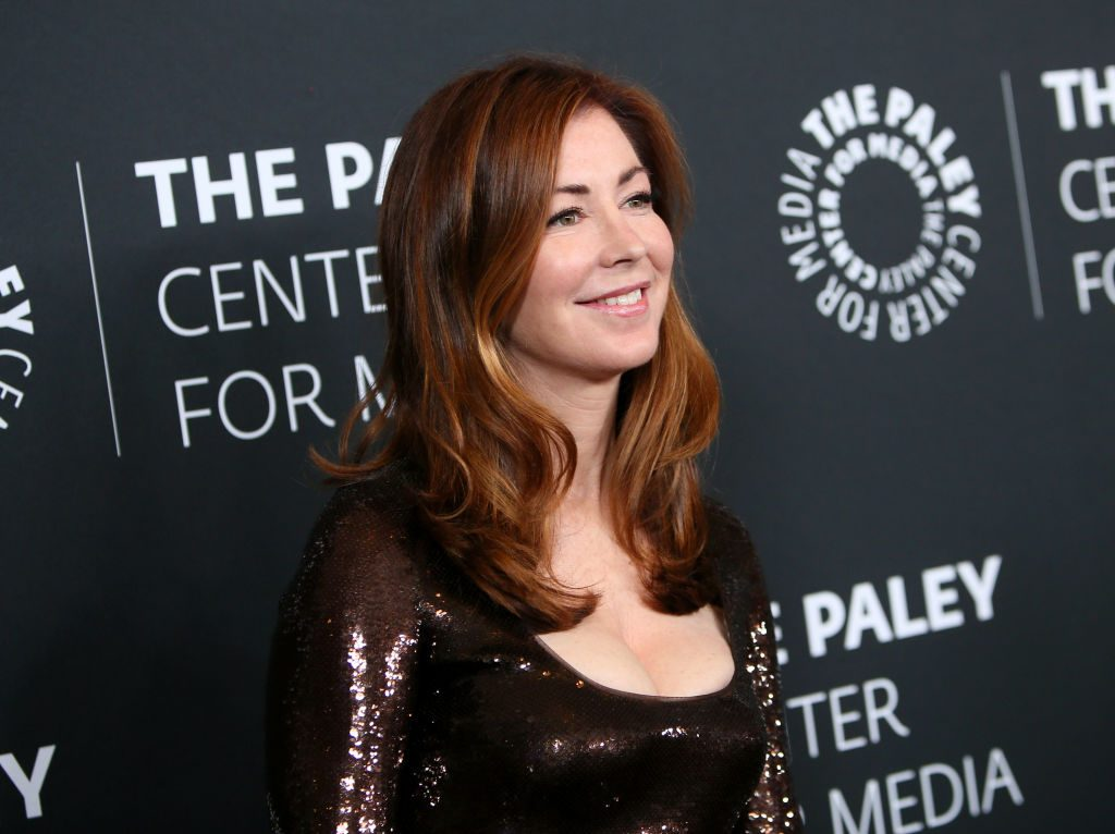Dana Delany looking off camera, standing in front of a repeating background