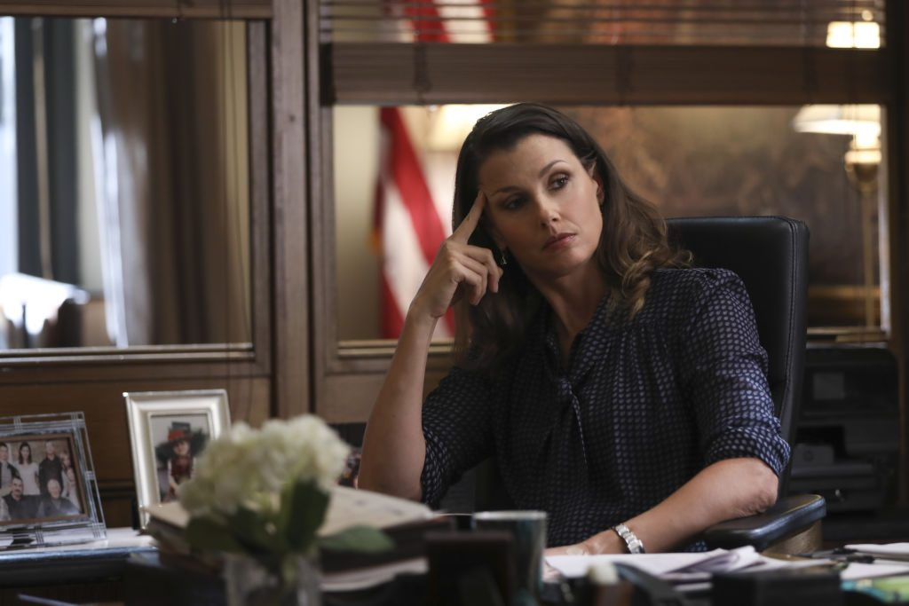 Bridget Moynahan as Erin Reagan on set of 'Blue Bloods' sitting at a desk with her head resting on her hand