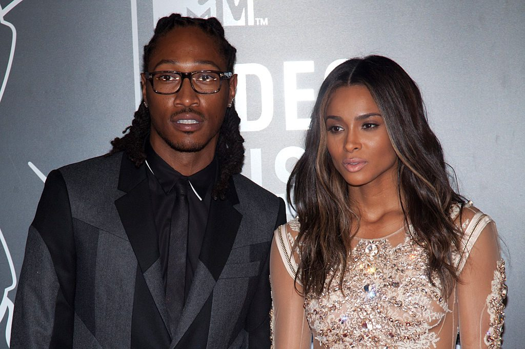 Future (left), wearing glasses and a black suit with Ciara (right) looking off camera in a gold jeweled dress