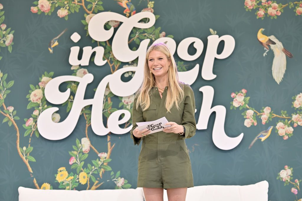 """Gwyneth Paltrow standing in front of a """"goop Lab"""" backdrop"""
