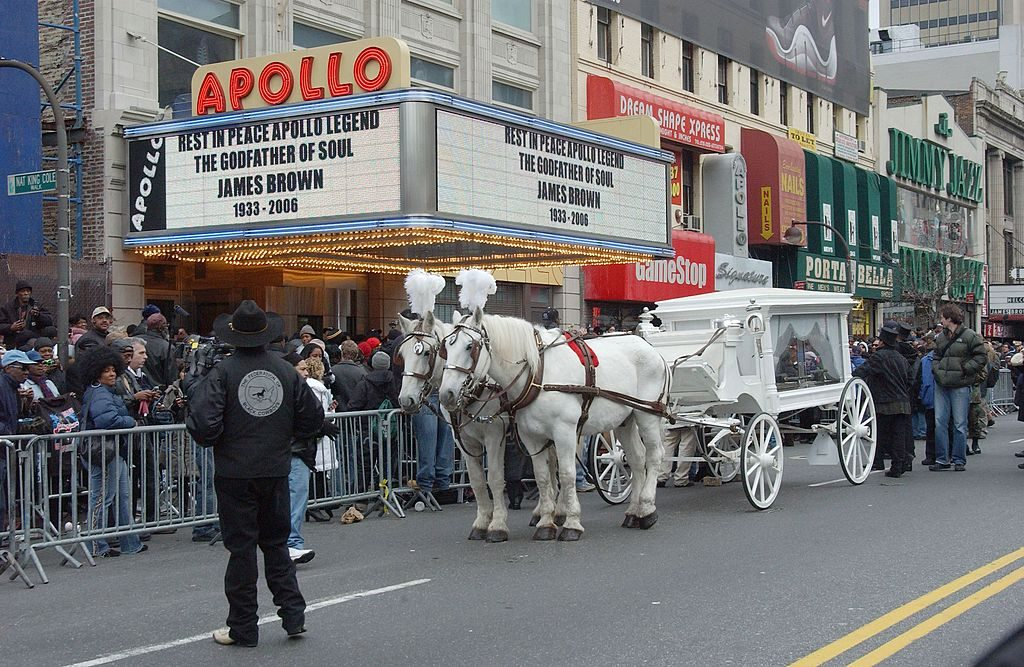 A horse-drawn carriage carrying the casket of James Brown