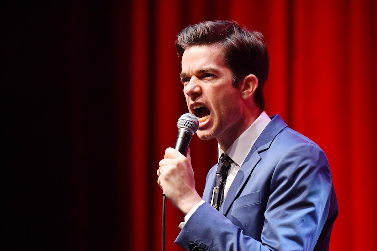 John Mulaney performs on stage