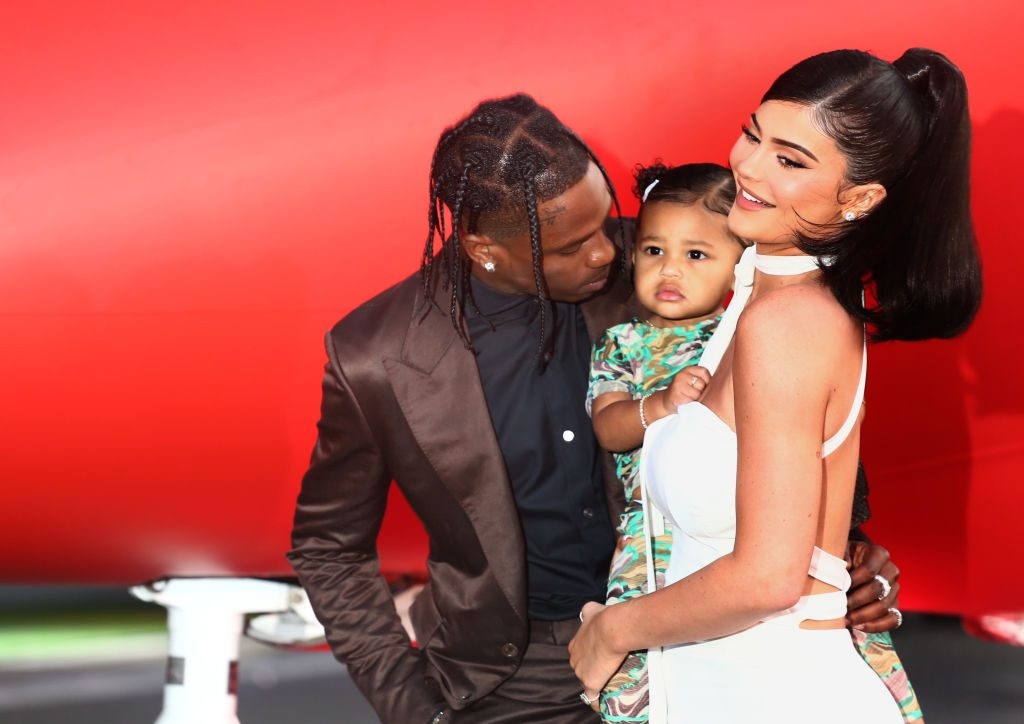 Kylie Jenner and Travis Scott holding Stormi on a red carpet
