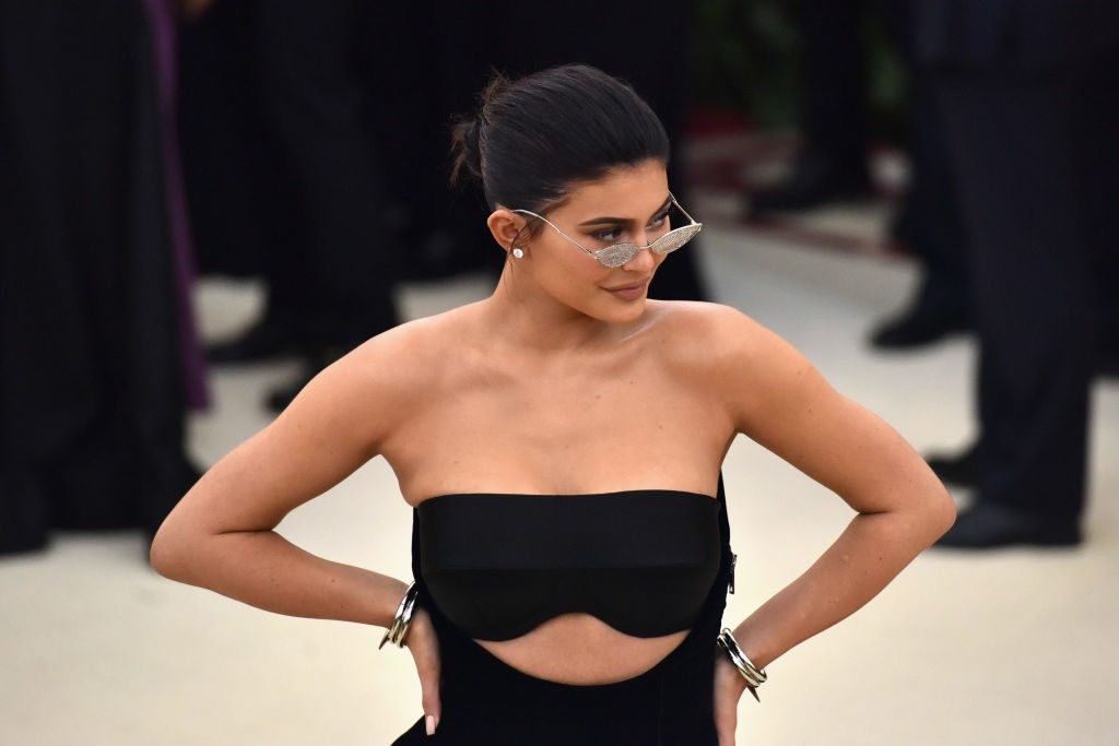 Kylie Jenner wearing sunglasses and a black dress, looking to the right