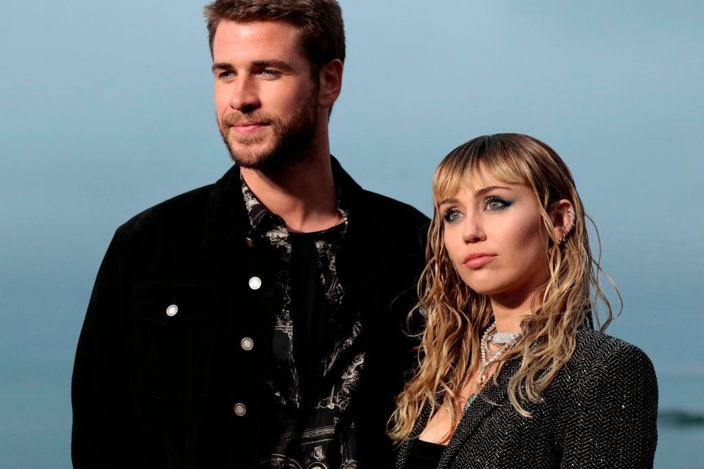 Miley Cyrus and Liam Hemsworth attain for the Saint Laurent Males's Spring-Summer season 2020 runway issue in Malibu
