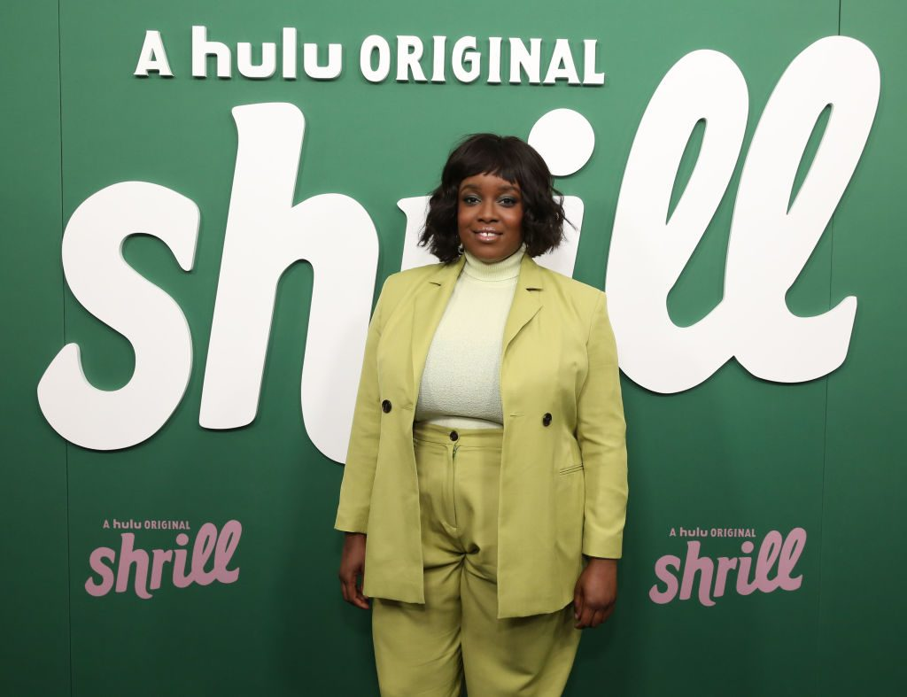 Lolly Adefope wearing green in front of a 'Shrill' promo backdrop