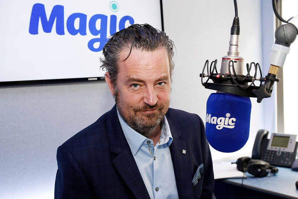 Matthew Perry in front of a microphone