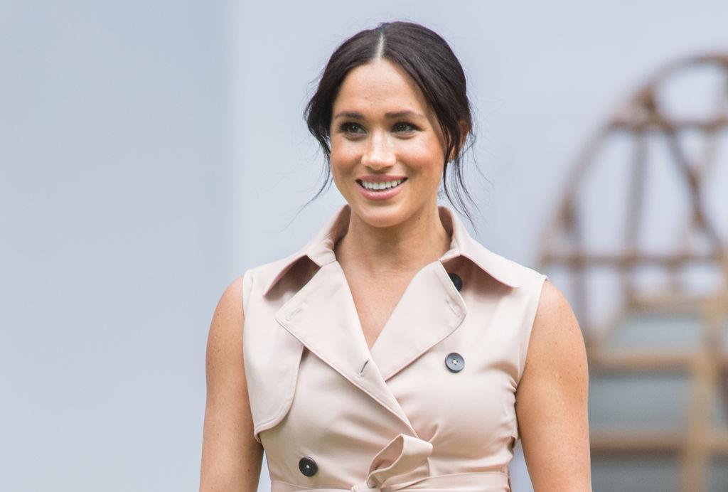 Meghan Markle smiling in a beige dress