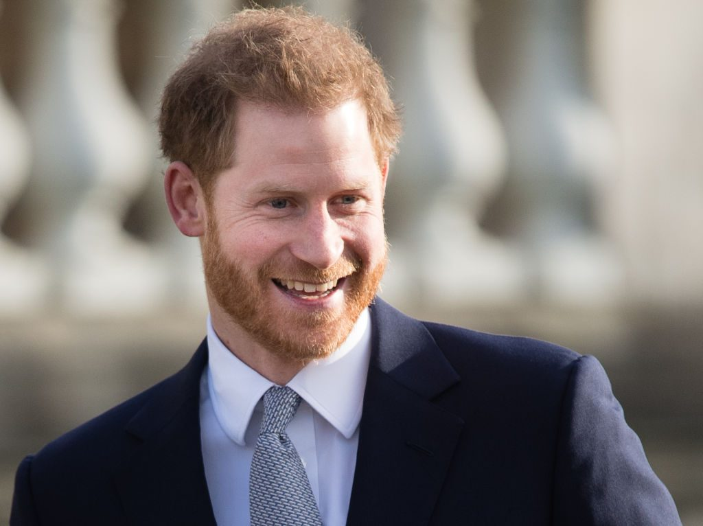 Prince Harry in a navy blue suit, smiling