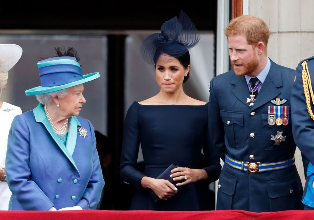 Queen Elizabeth II, Meghan Markle, and Prince Harry watch a flypast to mark the centenary of the Royal Air Force from the balcony of Buckingham Palace on July 10, 2018 in London, England. The 100th birthday of the RAF, which was founded on on 1 April 1918, was marked with a centenary parade with the presentation of a new Queen's Colour and flypast of 100 aircraft over Buckingham Palace. (Photo by Max Mumby/Indigo/Getty Images)