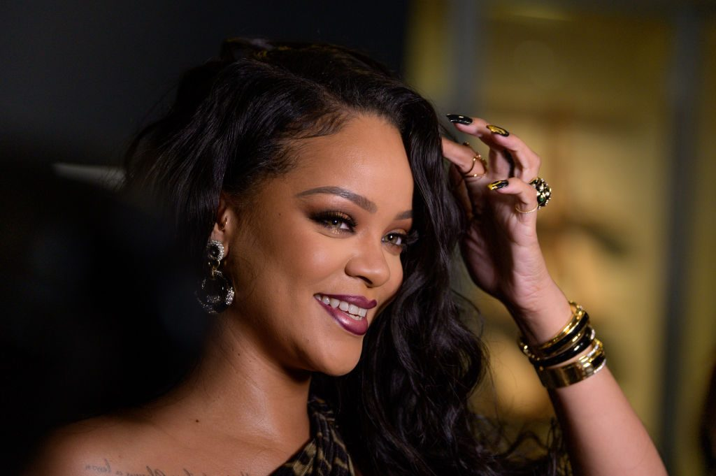 Rihanna touching her hair with gold accessories