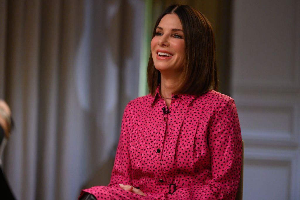 Sandra Bullock in a hot pink and black dotted shirt dress, smiling slightly off camera