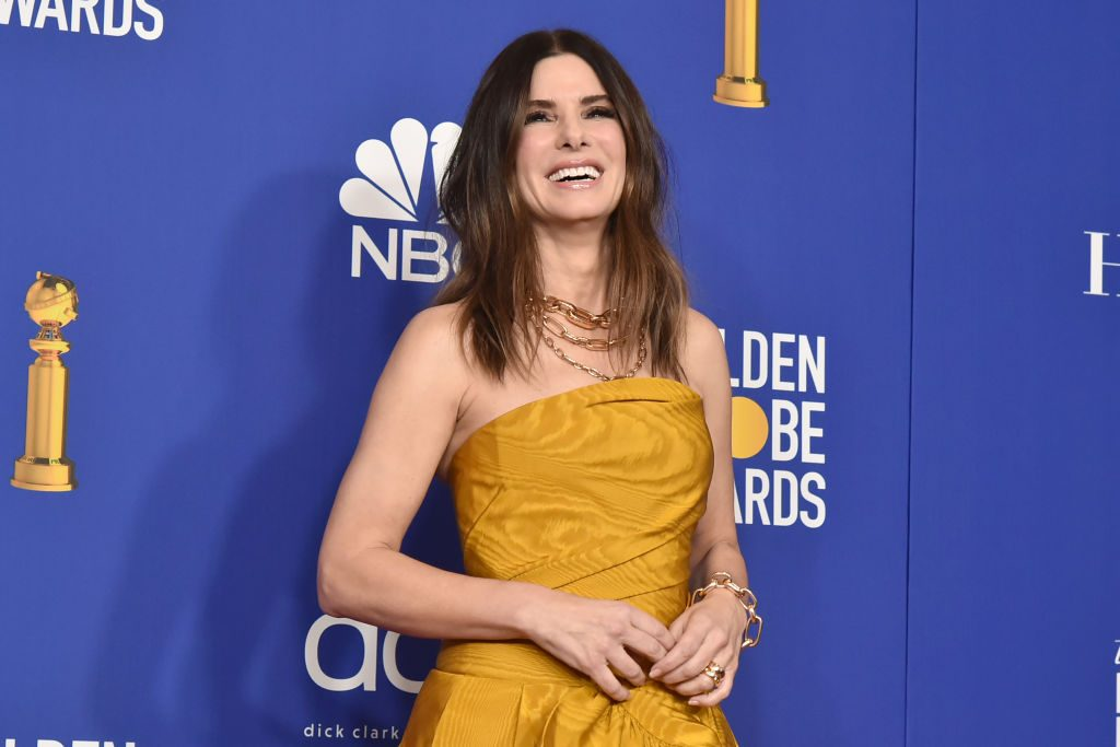 Sandra Bullock in yellow, laughing in front of the Golden Globes repeating background