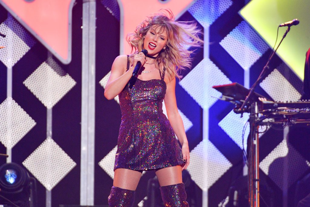 Taylor Swift in a glitter dress performing on stage
