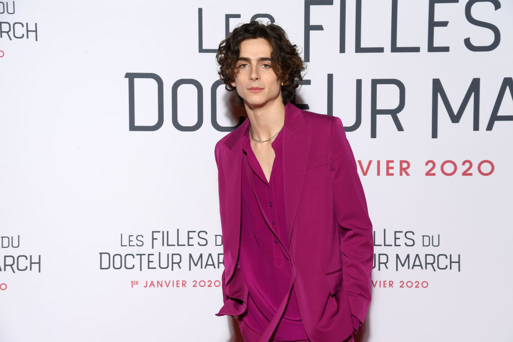 Timothée Chalamet wearing bright pink in front of a repeating background