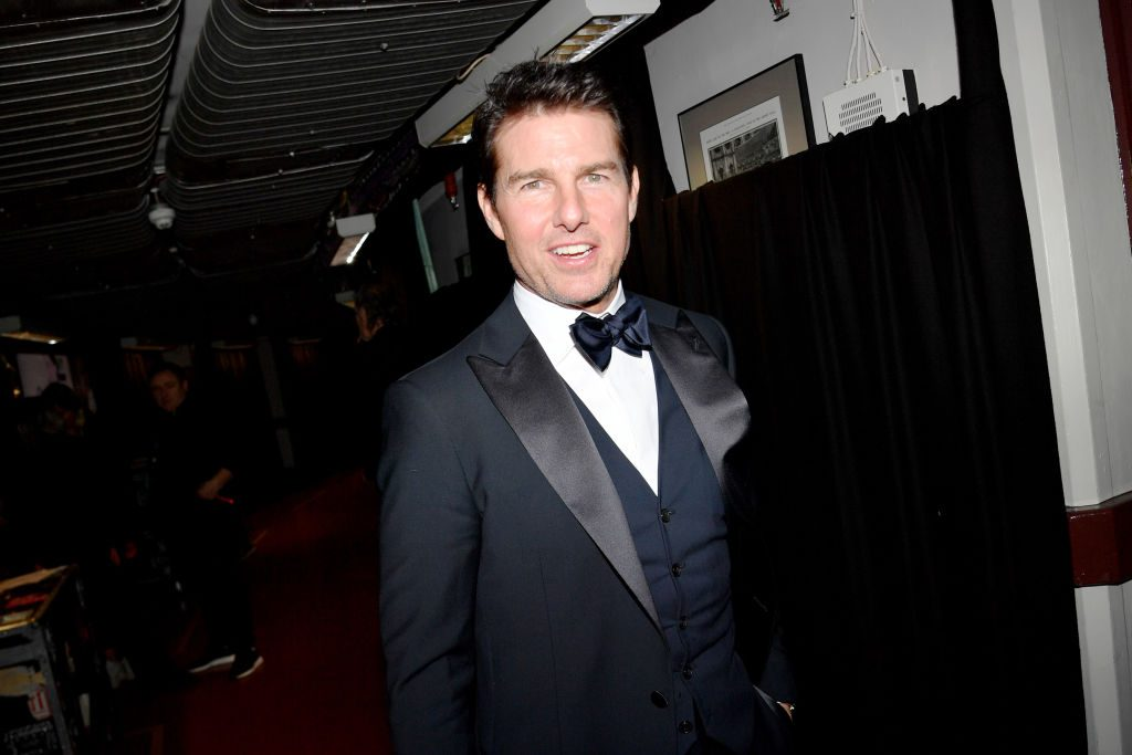 Tom Cruise in a navy suit, smiling at the camera