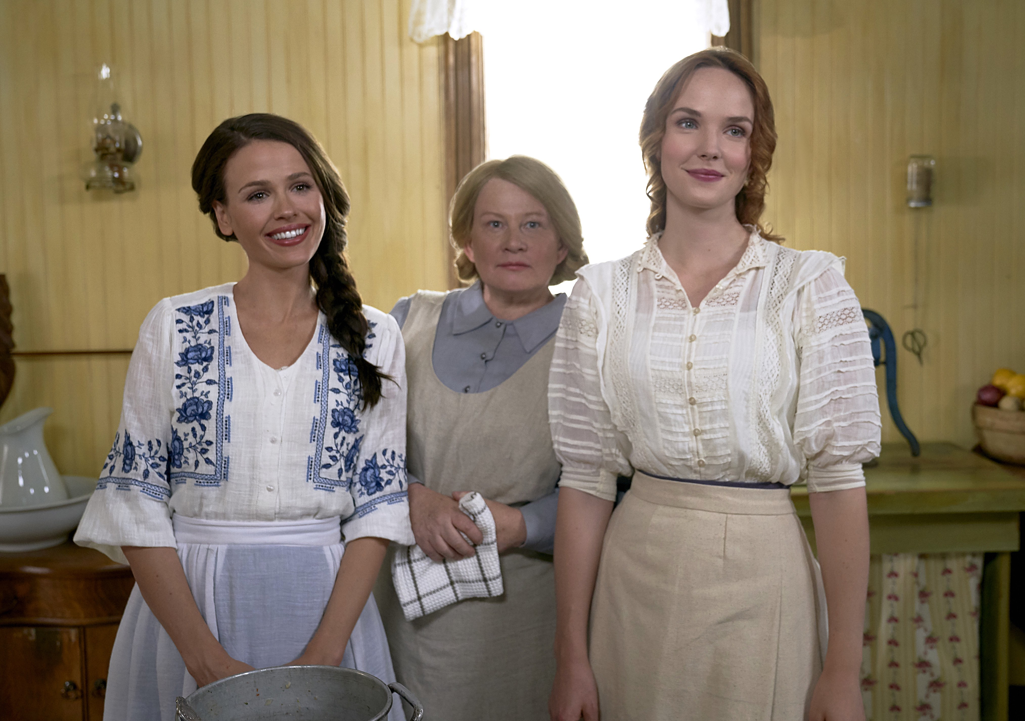 Grace and Lillian smiling with older woman in apron behind them in When Hope Calls