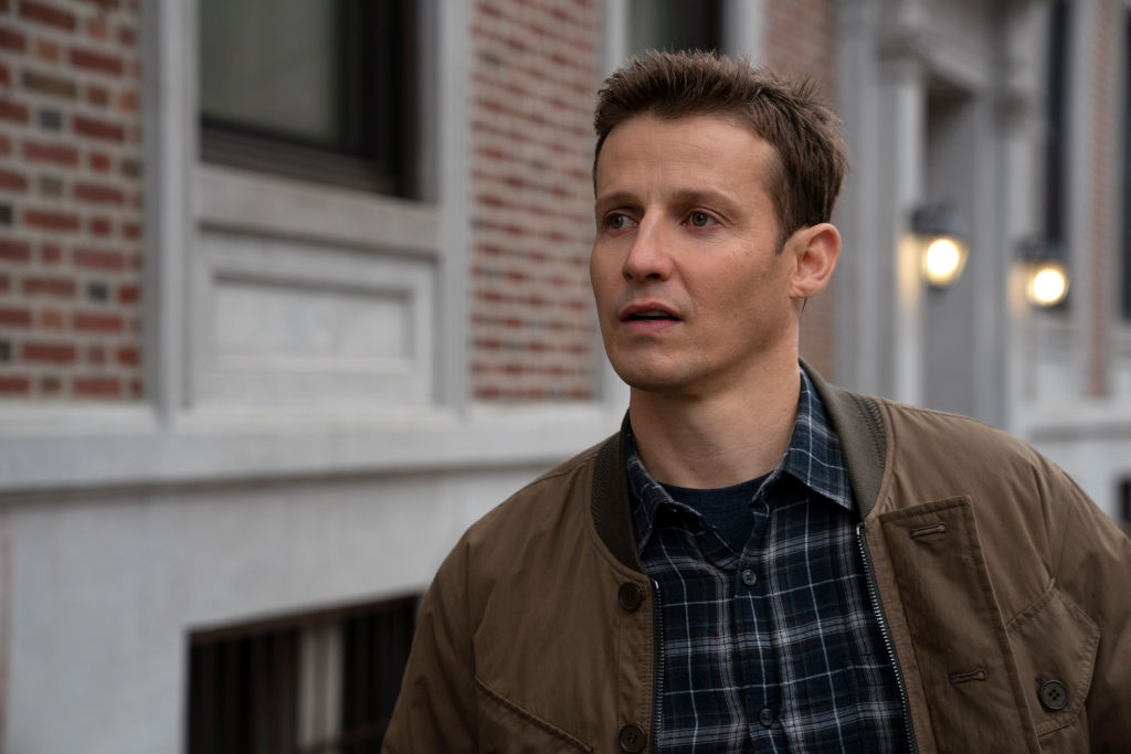 Will Estes looking off camera in a blue flannel shirt and brown jacket