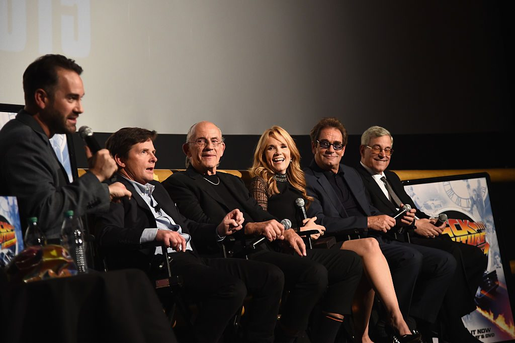Michael J. Fox, Christopher Lloyd, Lea Thompson, Huey Lewis, and Bob Gale speak onstage with moderator Aaron Sagers during the Back to the Future reunion