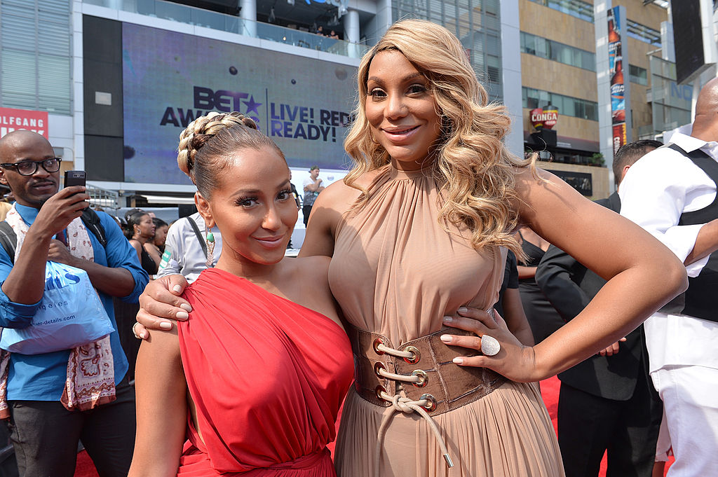 Adrienne Bailon and Tamar Braxton on the red carpet at an award show in 2013