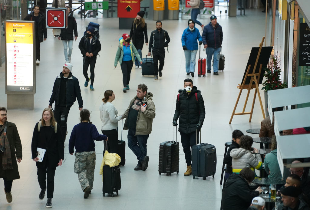 Travelers, including one man wearing a protective mask, walk in Terminal A at Tegel Airport before the Trump European travel ban goes into effect