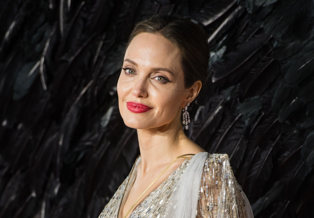 Angelina Jolie smiling in front of a textured background