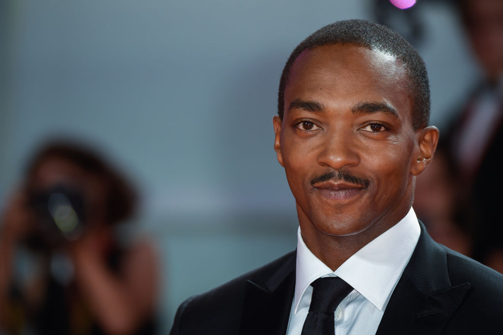 Anthony Mackie in a suit smiling at the camera