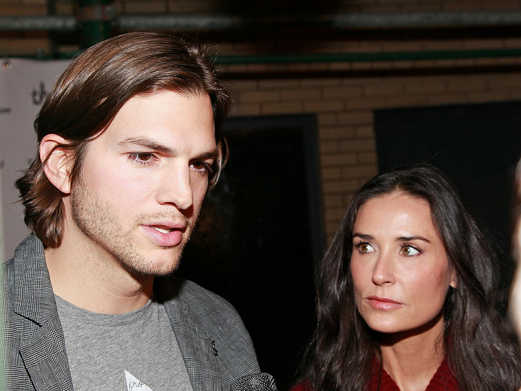 Ashton Kutcher talking and Demi Moore looking at Kutcher