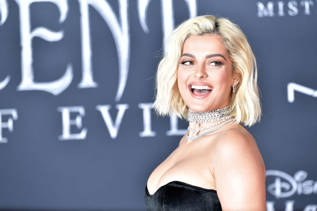 Bebe Rexha smiling in front of a repeating background