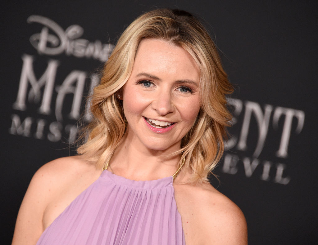 Beverley Mitchell smiling in front of a repeating background in a pink dress
