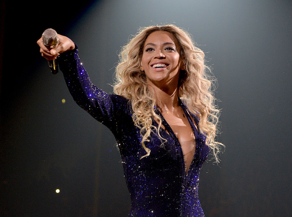 Beyoncé smiling, holding a microphone out to an audience