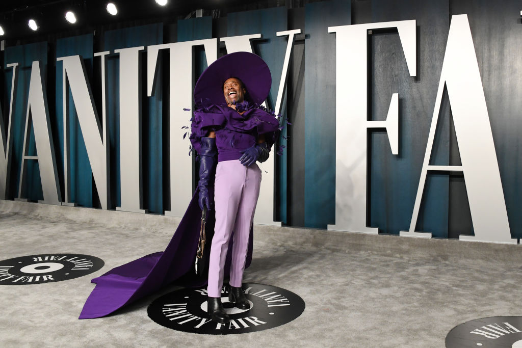 Billy Porter in an all purple outfit laughing